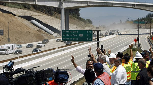 L.A. Mayor Villaraigosa and City Councilman Tom LaBonge join officials and media as they wave to the first motorists to travel under the Mulholland Drive bridge after the reopening of the 405 Freeway.