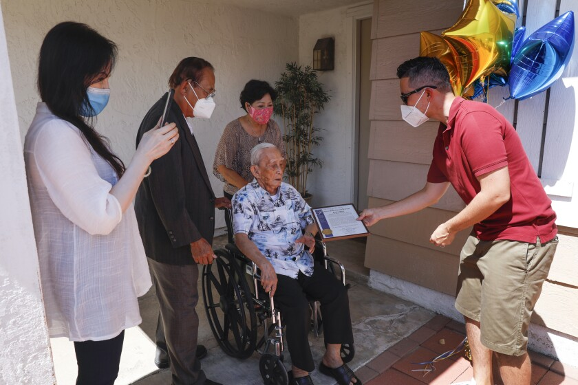 Khen Ngo, 109, of Mira Mesa, in wheelchair, receives a city proclamation Sunday from San Diego City Councilman Chris Cate.