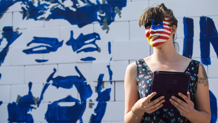 An activist with her face painted with the colors of the German and American flags joins a protest at the Brandenburg Gate in Berlin on Sept. 23.