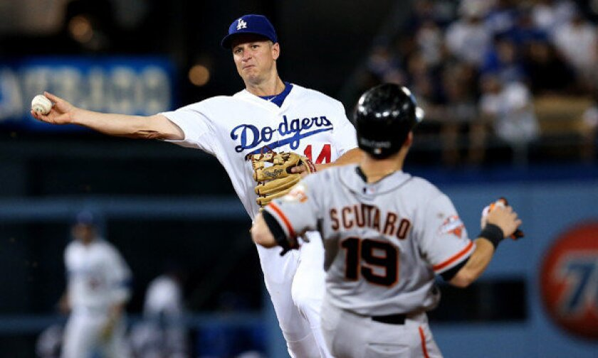 Dodgers second baseman Mark Ellis turns a double play in front of the Giants' Marco Scutaro during a game this summer.