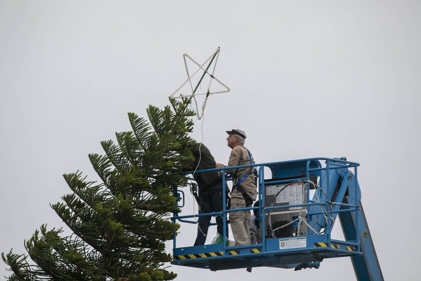 Ken Moss, right, and another volunteer with the Ocean Beach Town Council installed the star atop this years Ocean Beach Christmas tree at the foot of Newport Avenue on Tuesday, Dec. 3, 2019.