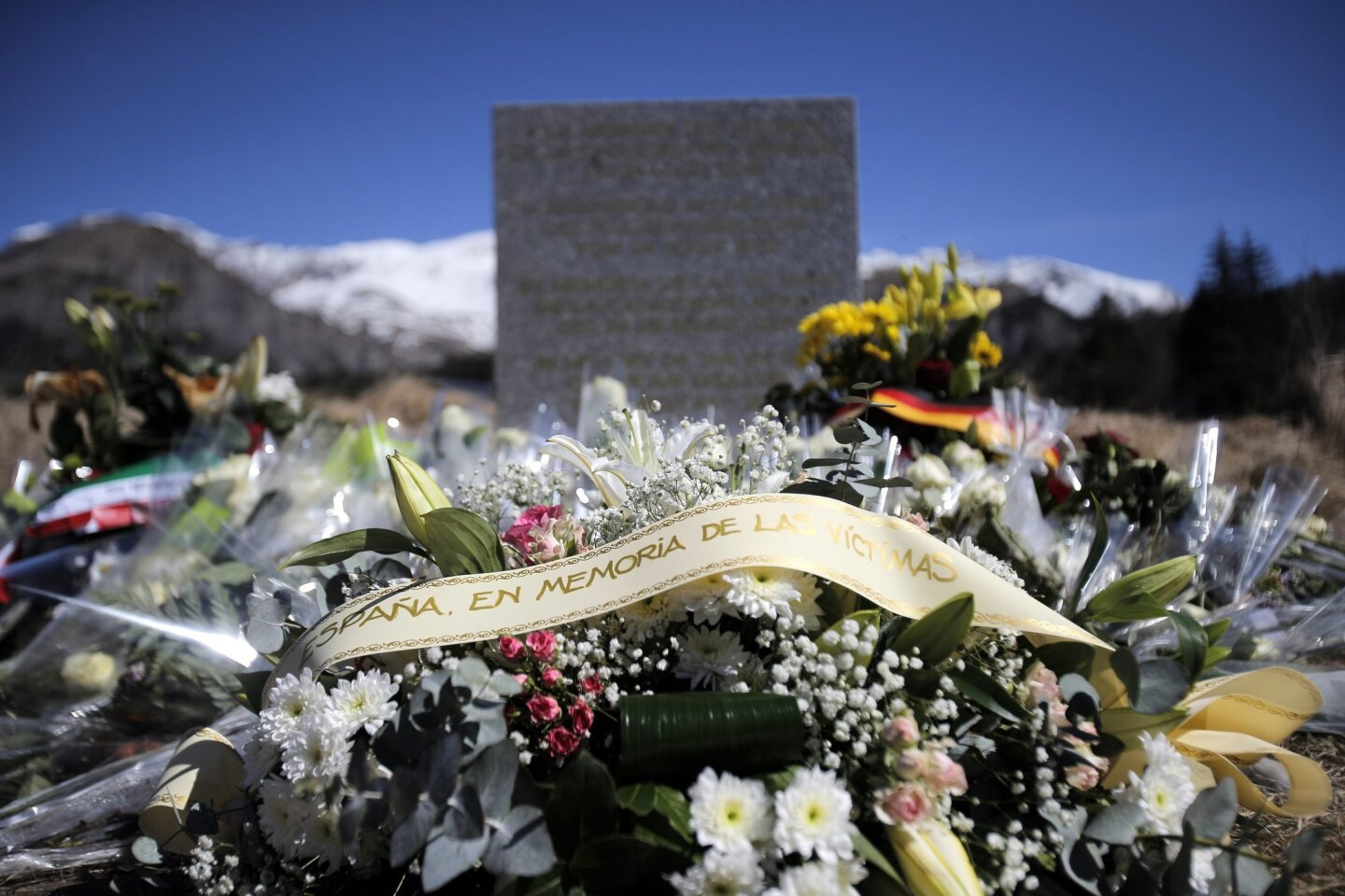 A stele and flowers laid in memory of the victims are placed in the area where the Germanwings jetliner crashed in the French Alps, in  Le Vernet, France, Friday, March 27, 2015. The crash of Germanwings Flight 9525 into an Alpine mountain, which killed all 150 people aboard, has raised questions a