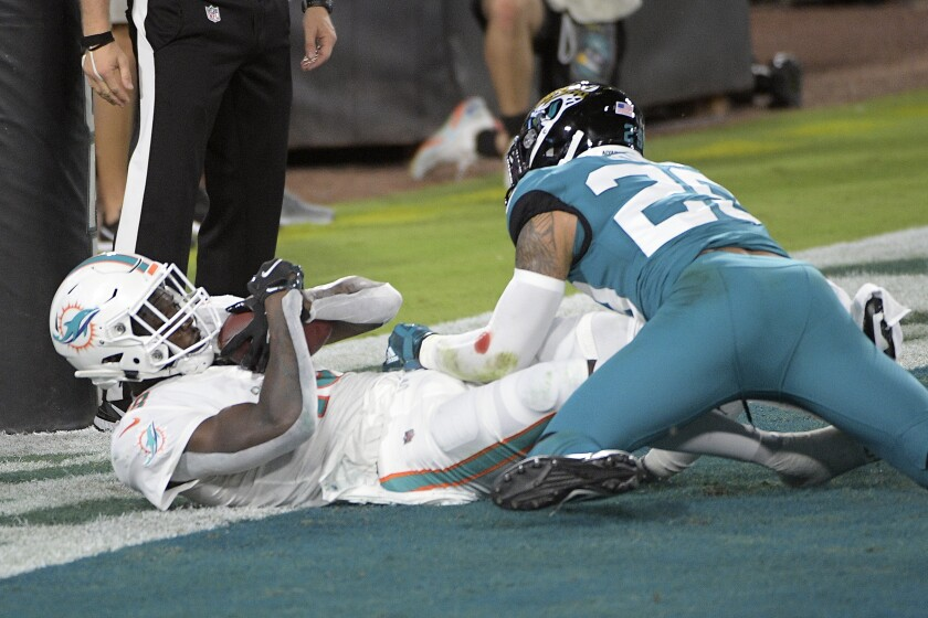 Miami Dolphins wide receiver Preston Williams, left, catches a pass in the end zone for a touchdown as Jacksonville Jaguars strong safety Josh Jones (29) tries to defend during the first half of an NFL football game, Thursday, Sept. 24, 2020, in Jacksonville, Fla. (AP Photo/Phelan M. Ebenhack)