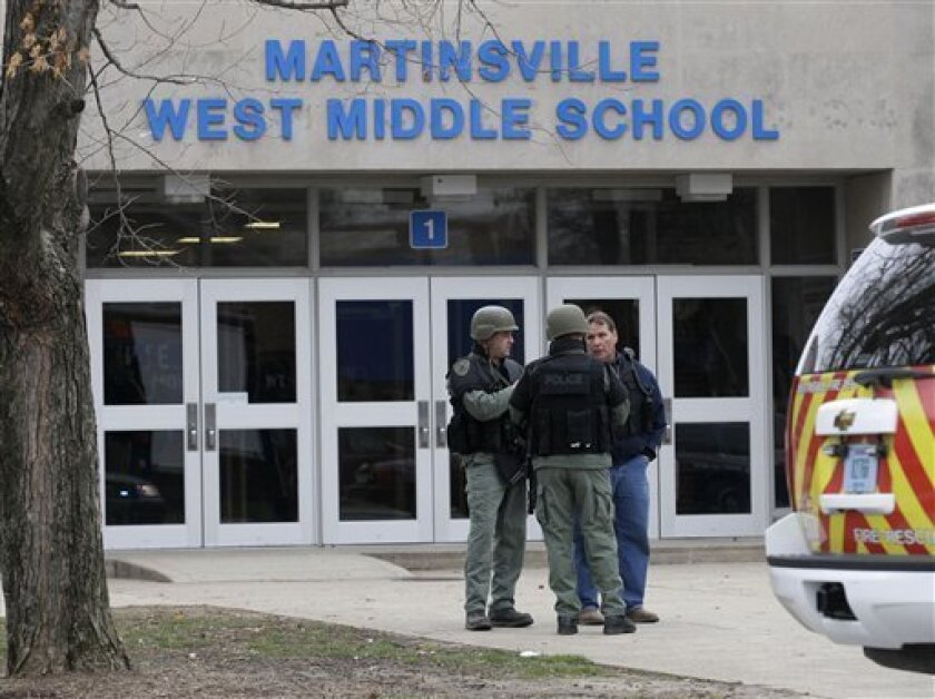 Police guard the front of the West Middle School in Martinsville, Ind., Friday, March 25, 2011. A teenage boy was shot at a central Indiana middle school shortly before classes began Friday and a fellow student is in custody, state police said. Sgt. Curt Durnil said the victim and a 15-year-old suspect are both students at Martinsville West Middle School where the shooting took place. (AP Photo/Darron Cummings)