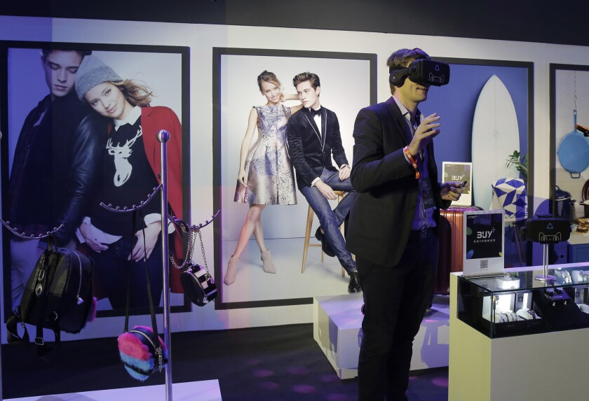 """A man wearing a viewer headset experiences augmented reality intelligent for shopping at an exhibition during the """"Singles' Day"""" global online shopping festival in Shenzhen, southern China's Guangdong province Friday, Nov. 11, 2016. In a bright spot for China's cooling economy, online shoppers spent billions of dollars Friday on """"Singles Day,"""" a quirky holiday that has grown into the world's busiest day for e-commerce."""