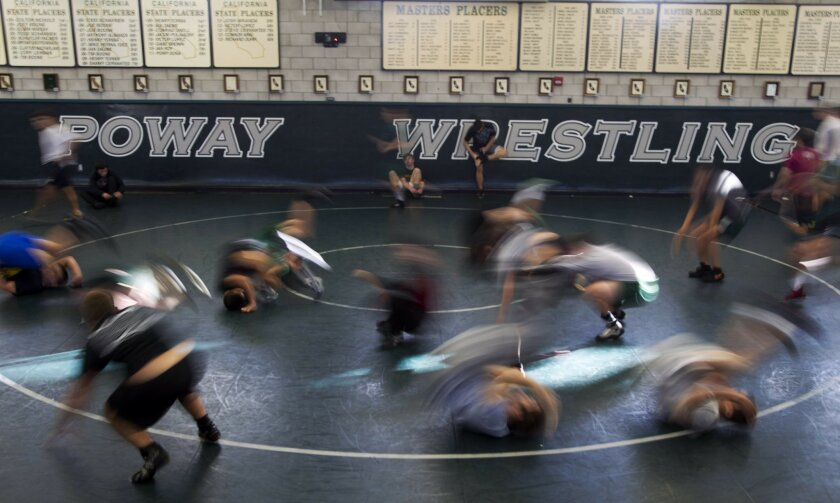 Poway wrestlers warm up at the start of practice.