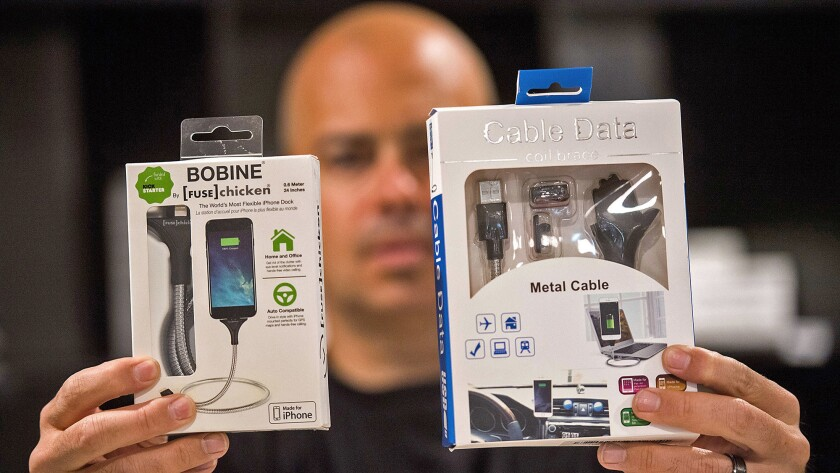 Jon Fawcett holds one of his company's items on the left and the counterfeit item he purchased on Am