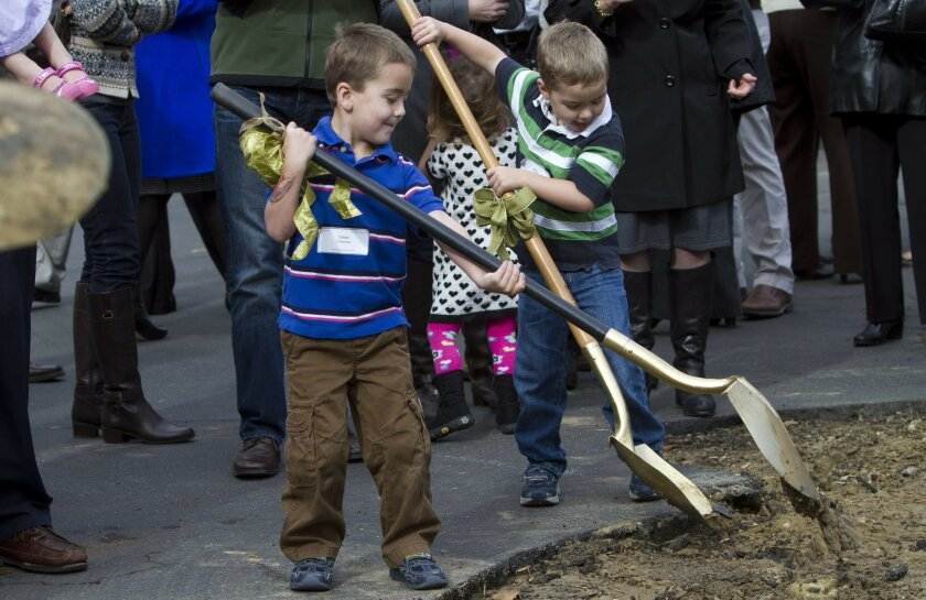 Twin boys, Drew, left, and Will Cavaniss, 5, get their hands on shovels and turn a little earth during a ground breaking ceremony for a 2-story, 16,000 square-foot children's ministry building Sunday at the Solana Beach Presbyterian Church.