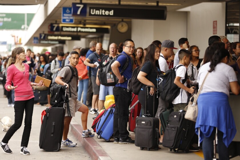 Passengers wait in long lines at the United Airlines terminal at LAX after a nationwide flight stoppage on July 8.