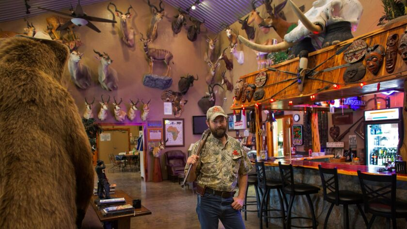 Philip Glass stands in a trophy room at the SAAM Safari Training School at the FTW Ranch in Texas. T
