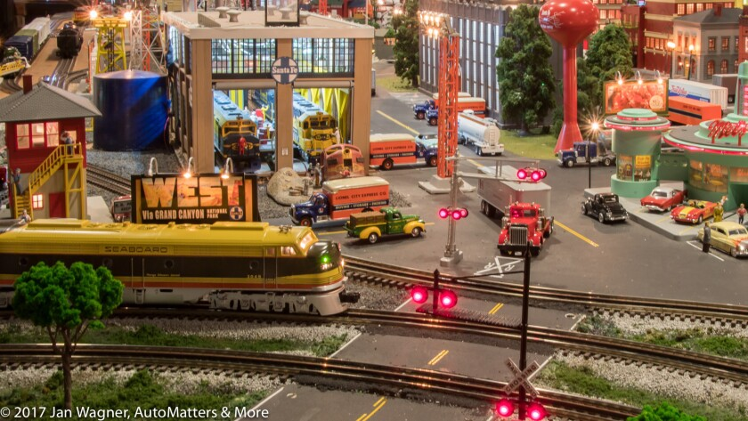 Scale model train approaching a railway crossing