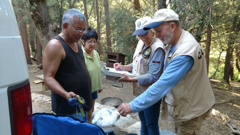 Palomar Mountain State Park campground hosts Lydia and Randy Marrs (right) speak with campers Len an