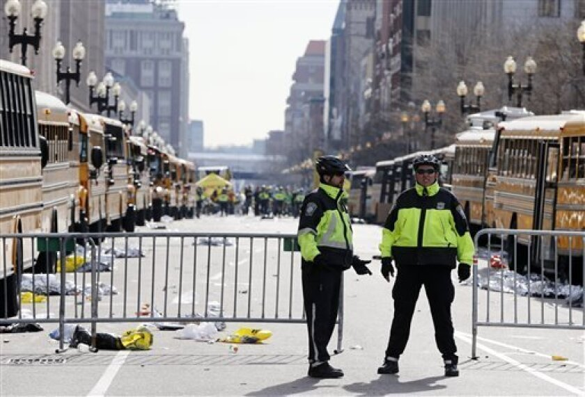 Boston police officers stand on Boylston Street near empty buses meant to transport runners who were instead diverted from the course following an explosion at the finish line, Monday, April 15, 2013, in Boston. (AP Photo/Michael Dwyer)