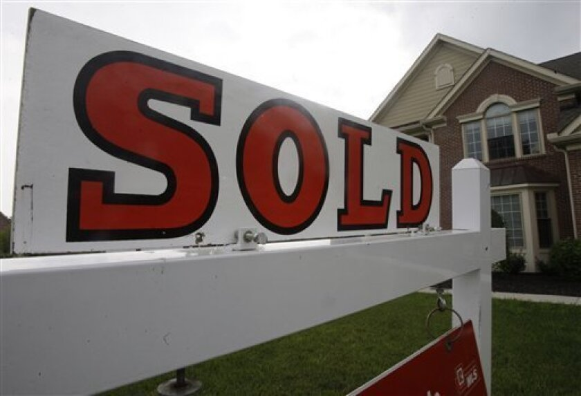 In this June 2, 2010 photo, a sold sign is posted outside a home, in Cincinnati. Rates on 30-year fixed mortgages fell this week to the lowest level of the year and were barely shy of the all-time low.(AP Photo/Al Behrman)