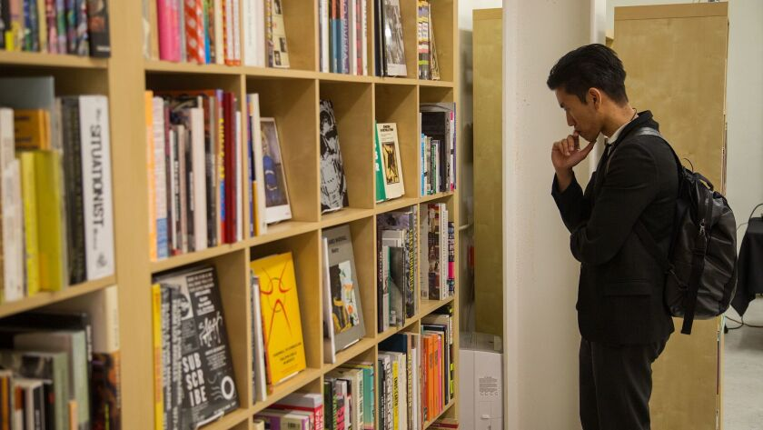 LOS ANGELES, CA - MARCH 31, 2017: A customer browses through at book titles at Other Books, a neighb