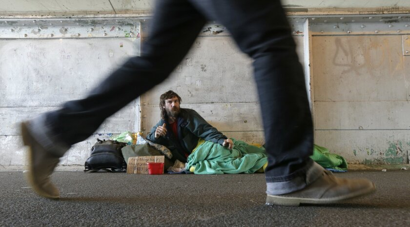 Harold McDuffie II, who says he has been homeless for three years, watches pedestrians pass by as he lies in a sleeping bag on a bridge leading to the ferry dock in downtown Seattle on Tuesday, Feb. 9, 2016. Seattle has the third-highest number of homeless people in the U.S. (AP Photo/Ted S. Warren