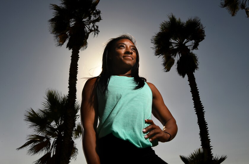 Simone Biles is framed by palm trees.