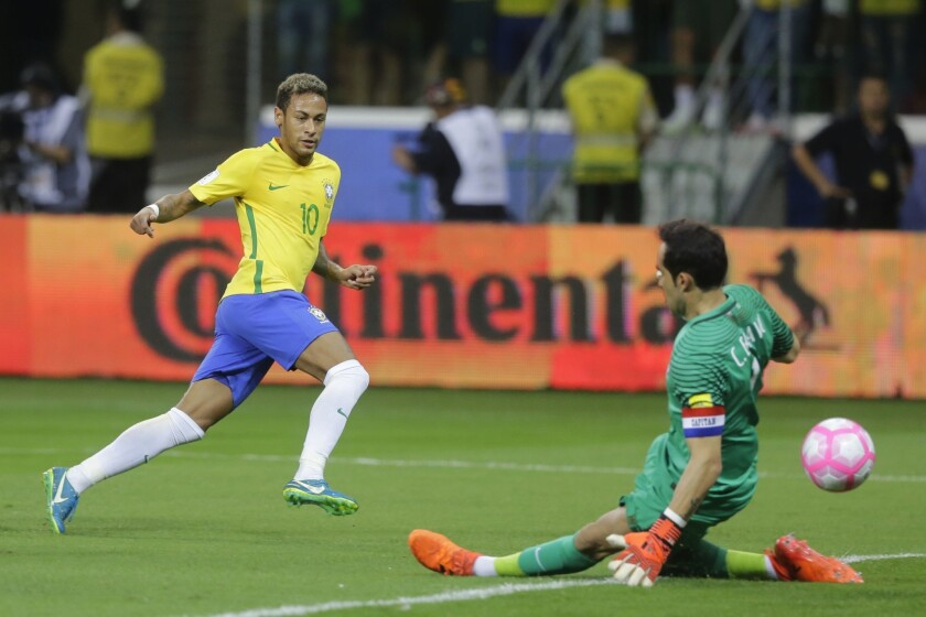 Brazil's Neymar kicks the ball past Chile goalkeeper Claudio Bravo, right, during a World Cup qualifying soccer match in Sao Paulo, Brazil.