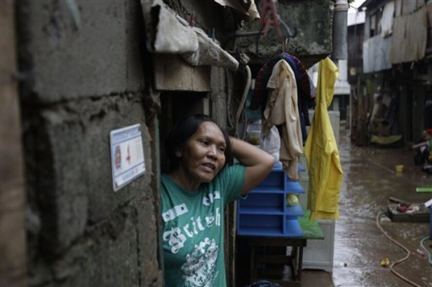 Luzviminda Limas goes out of their house after floods recede in suburban Marikina city, east of Manila, Philippines on Friday Aug. 10, 2012. The 54-year-old widow said the floods this week brought back memories of the 2009 deluge when she was huddled under an umbrella with one of her two daughters and her four-month old grandson on the roof of a day-care center beside her house as floodwaters rampaged through her neighborhood during a typhoon. The flood then destroyed her home. (AP Photo/Aaron Favila)