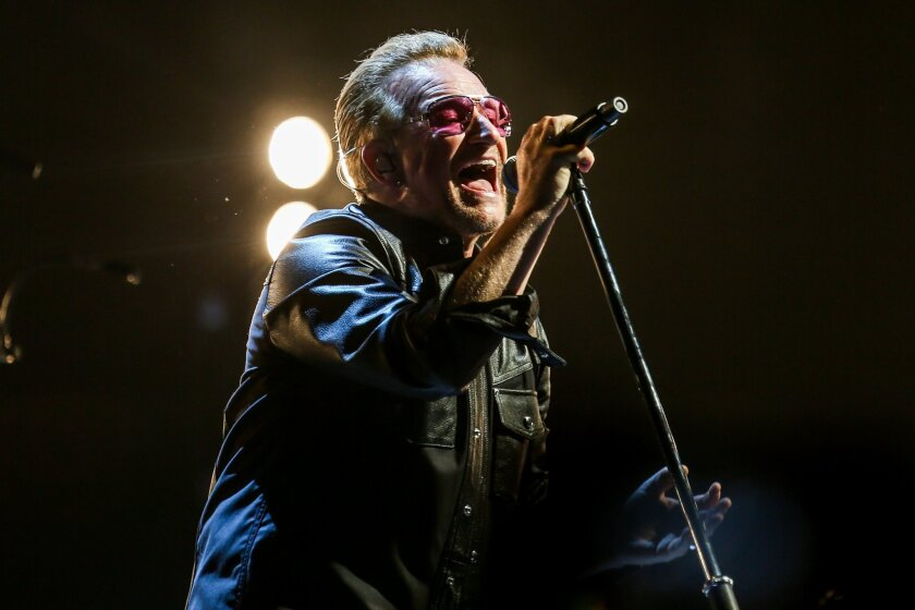 U2 singer Bono performs at the Forum. The band members honored late tour manager Dennis Sheehan at their Wednesday night show.