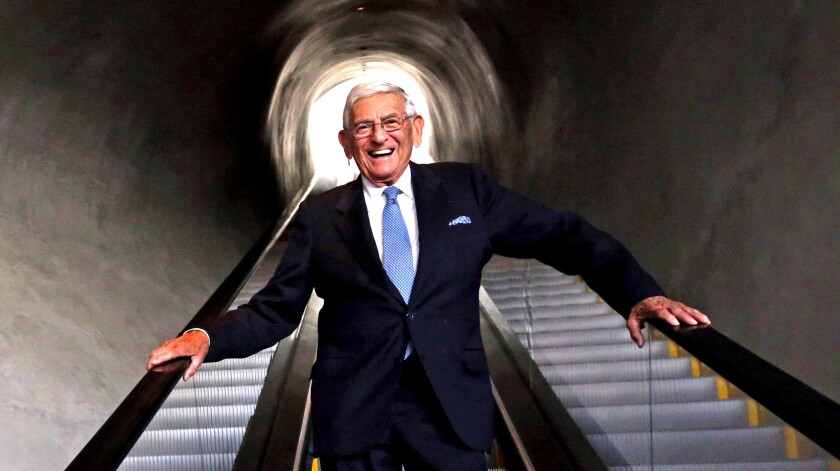 Eli Broad stands on an escalator in the Broad museum.