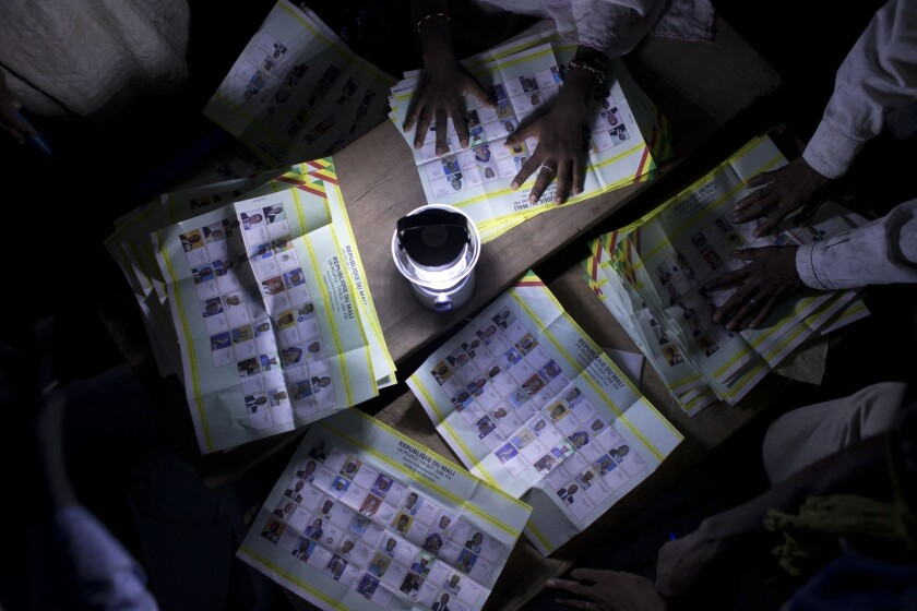 Election workers count votes at a station that reported a high voter turnout in Kidal, Mali, on Sunday.