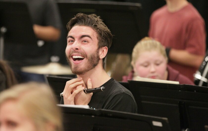 """Piccolo player Kevin Moore laughs at his efforts while rehearsing a part of """"Variations on America"""" during rehearsal for the San Diego Civic Youth Orchestra at Classical Academy High School in Escondido."""