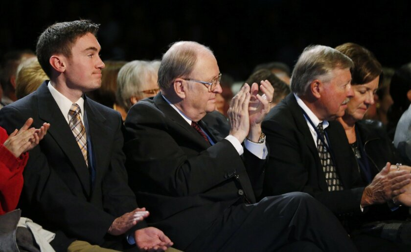 FILE - In this Thursday, Oct. 29, 2015, file photograph, Bill Armstrong, center, president of Colorado Christian University and retired U.S. senator from Colorado, applauds while listening to Republican presidential candidate Ben Carson during a campaign stop at a religious college in Lakewood, Col