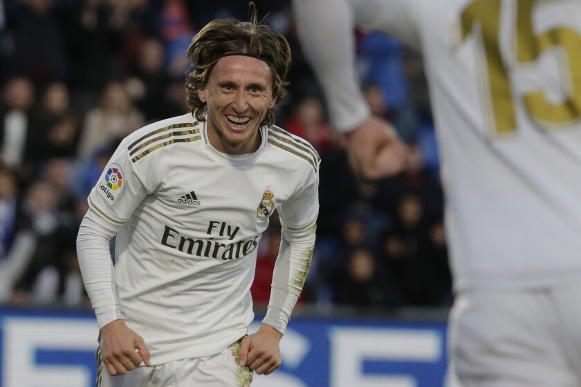 Real Madrid's Luka Modric, left, celebrates with teammate Federico Valverde after scoring his side's third goal during a Spanish La Liga soccer match between Getafe and Real Madrid at the Coliseum Alfonso Perez stadium in Getafe, Spain, Saturday, Jan. 4, 2020. (AP Photo/Paul White)