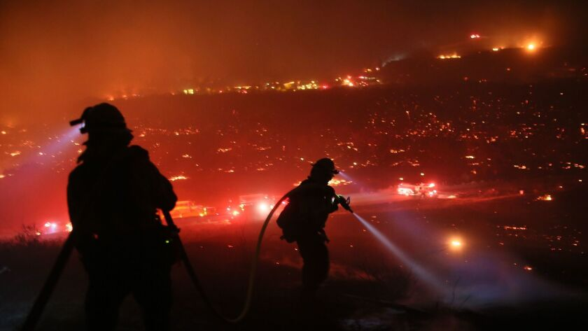 Firefighters battle the Lilac Fire in Bonsall in December 2017. A bill aimed at trying to reduce the risk of wildfires in California is making its way through the 2018 Legislature but has met resistance from some quarters.