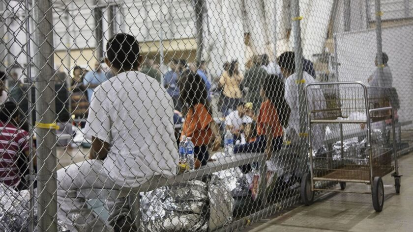 People who've been taken into custody related to cases of illegal entry into the United States sit in one of the cages at a facility in McAllen, Texas, on June 17.