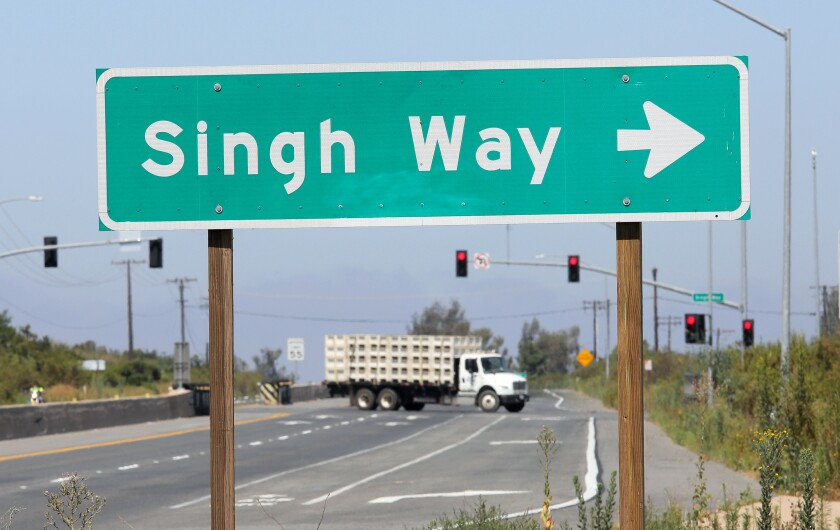 An agriculture truck for carrying tomatoes turns onto Singh Way from Highway 76 to go to the Singh family's West Coast Tomato Growers' headquarters, warehouse and packing facility adjacent to their hundreds of acres of tomatoes.