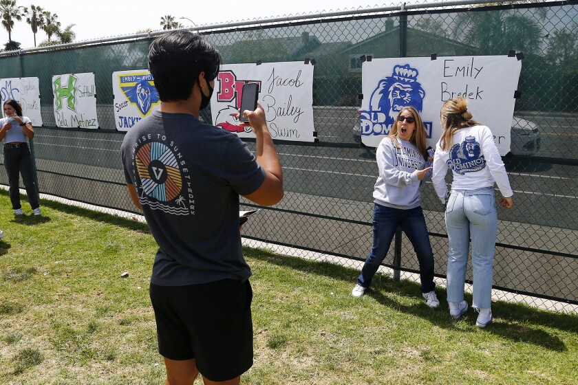 Mateo Liau, left, takes a photo of his girlfriend Emily Bredek, far right, as she poses with her mother Julia.