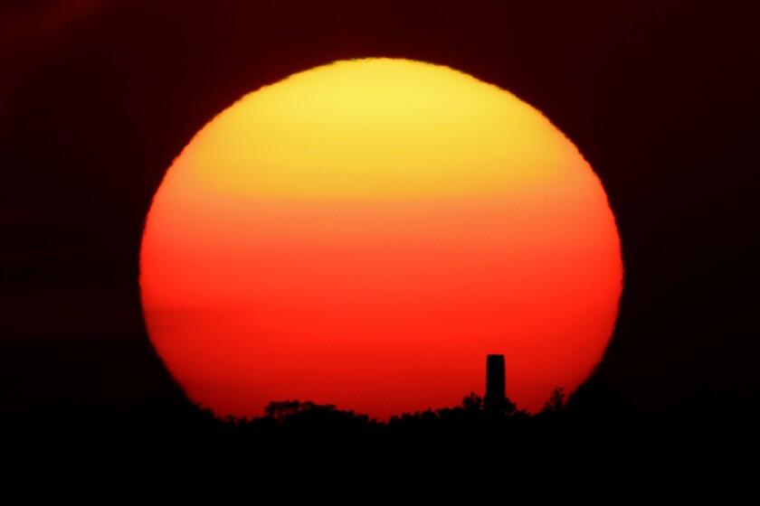 The bright orange sun silhouettes a smokestack