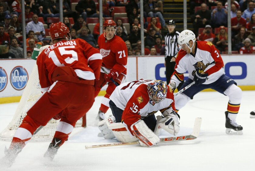 Florida Panthers goalie Al Montoya (35) stops a Detroit Red Wings shot with defenseman Steven Kampfer (3) as Detroit Red Wings center Riley Sheahan (15) and Detroit Red Wings center Dylan Larkin (71) wait for a rebound in the second period of an NHL hockey game, Monday, Feb. 8, 2016 in Detroit. (AP