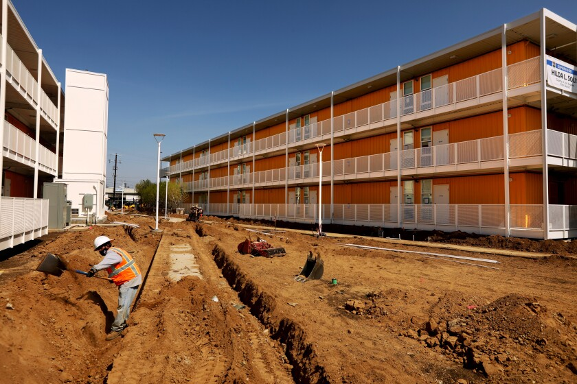 A worker digs a trench on the grounds between two brightly painted three-story towers made of shipping containers
