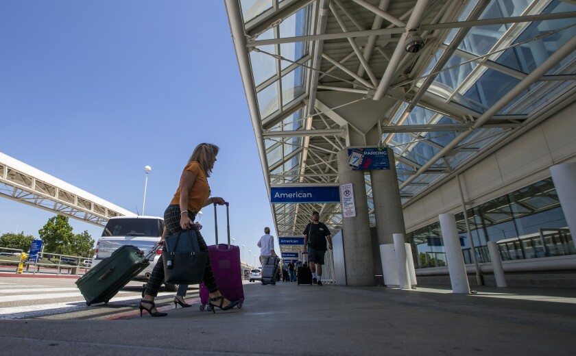 A woman with a suitcase heads into a terminal at Ontario International Airport prepandemic.