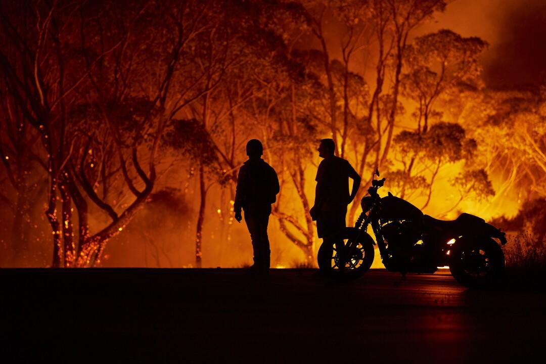 Residents watch as flames burn through bush in Lake Tabourie, Australia.