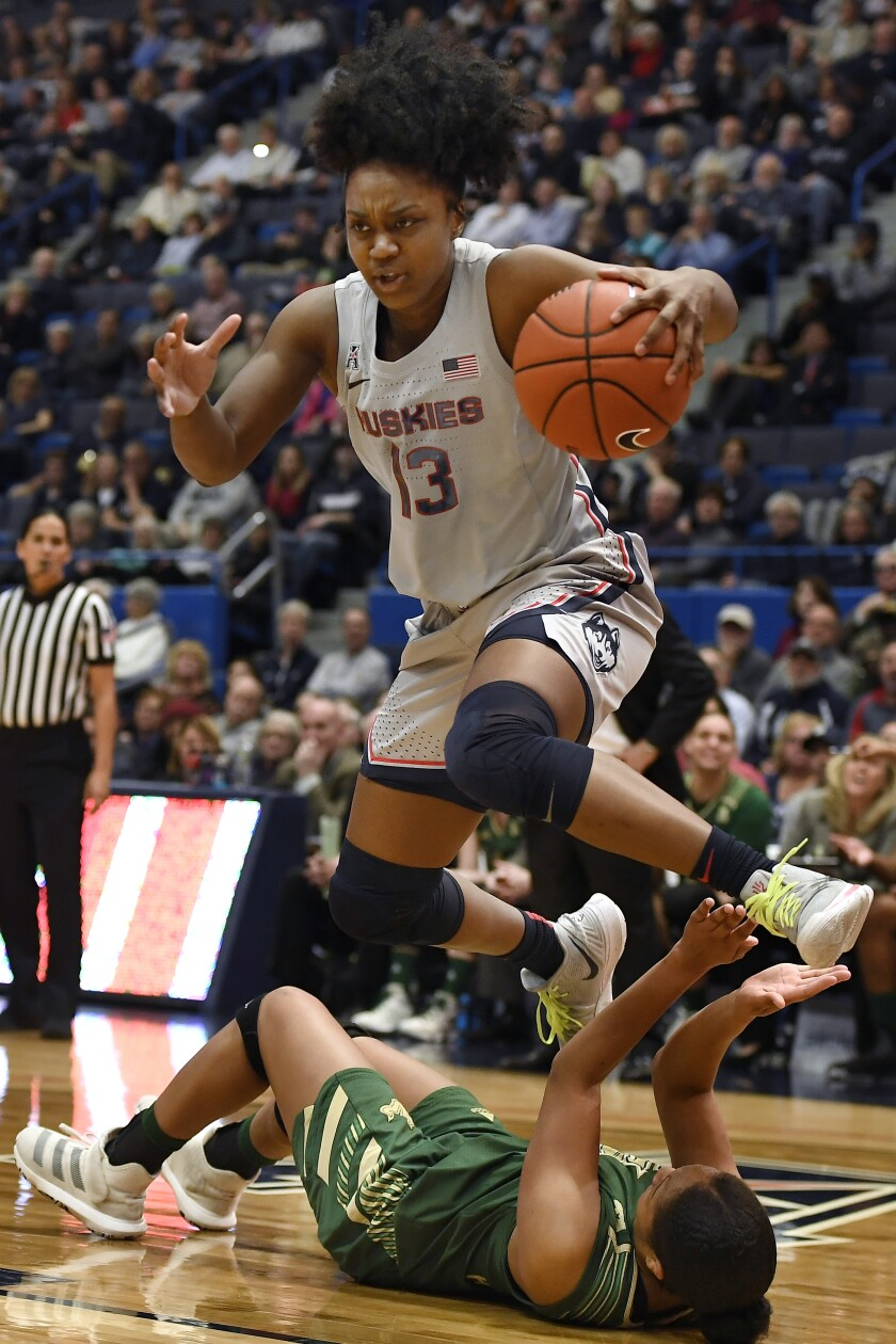 Connecticut's Christyn Williams (13) jumps over South Florida's Sydni Harvey in the first half of an NCAA college basketball game, Monday, March 2, 2020, in Hartford, Conn. (AP Photo/Jessica Hill)
