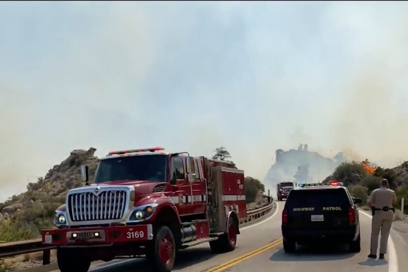 A fire truck and a police SUV with smoke in the background