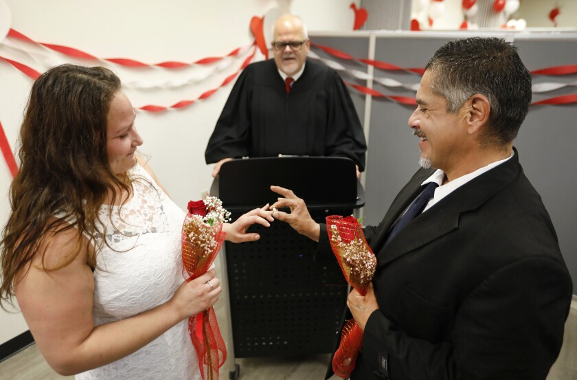 NORWALK, CA - FEBRUARY 14, 2019 Miguel Rodriguez, places a ring on the finger of his bride Donna Ro