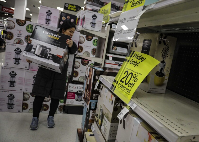 FILE - In this Nov. 29, 2019, file photo a shopper carries a crockpot during Target's Black Friday sale in the Borough of New York. Shopping at sales and using coupons may not be saving you as much money as you think. Knowing the pitfalls and having a plan can help keep your holiday shopping from coming back to bite you in January. (AP Photo/Bebeto Matthews, File)
