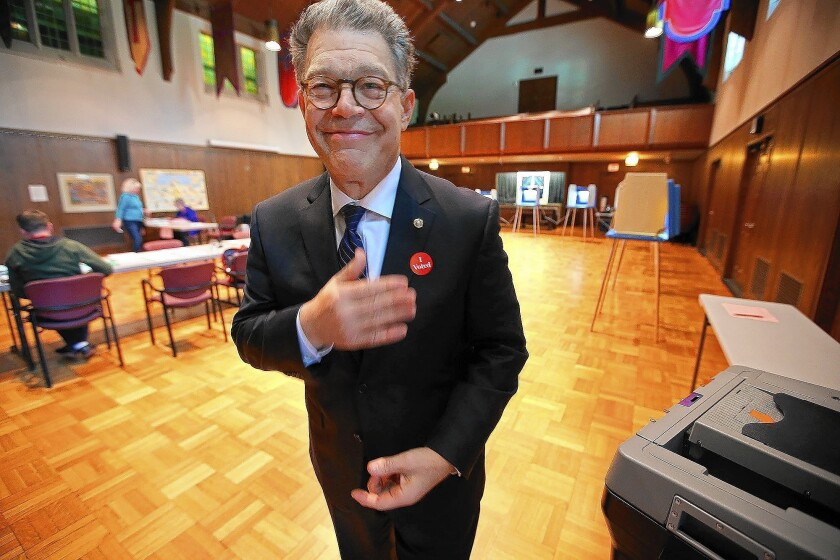 """Sen. Al Franken (D-Minn.) places an """"I voted"""" sticker on his coat at a polling station in Minneapolis after casting his ballot in the primary. He won the Democratic nomination overwhelmingly and will face Republican Mike McFadden in November."""