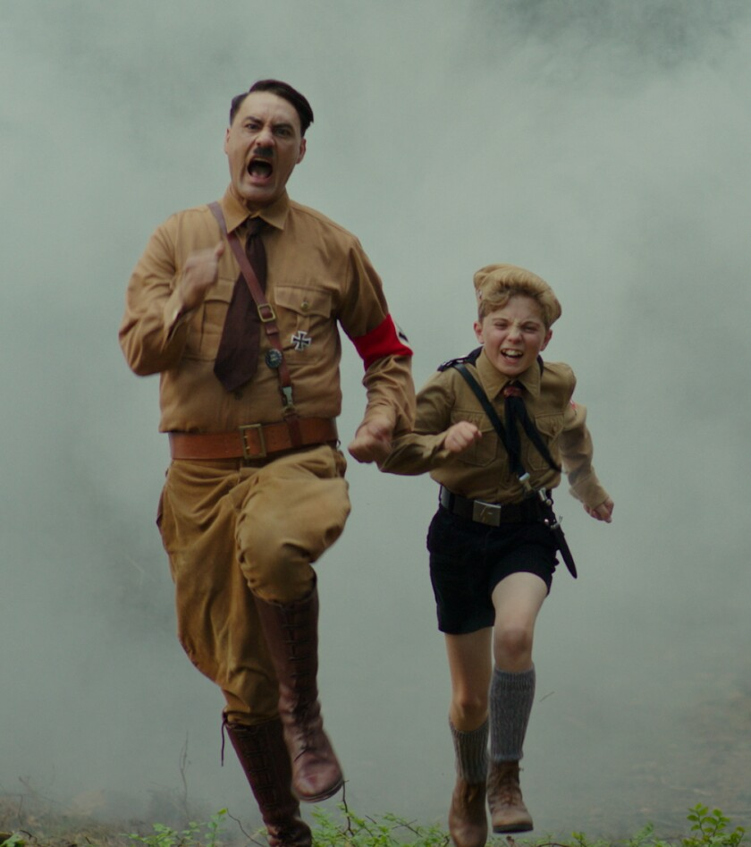 "Actor-director Taika Waititi and young Roman Griffin Davis run from an explosion in ""Jojo Rabbit."""