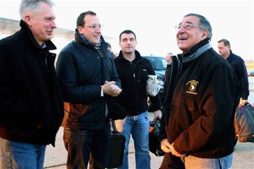 Outgoing Defense Secretary Leon Panetta, right, talks with Marine Lt. Gen. Thomas Waldhauser, left, and assistant Defense Department press secretary Carl Woog, second from left, before boarding a E-4B aircraft at Andrews Air Force Base, Md., Wednesday, Feb. 20, 2013, before traveling to Brussels fo