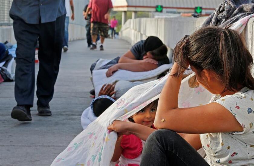 Jennifer, de 2 años, y su madre Evelyn (dcha) aguardan en un puente cerca de la frontera entre EE. UU. y México junto a otros solicitantes de asilo de Guatemala y Cuba en espera de poder entrar EE.UU. en Matamoros (México). EFE/Archivo