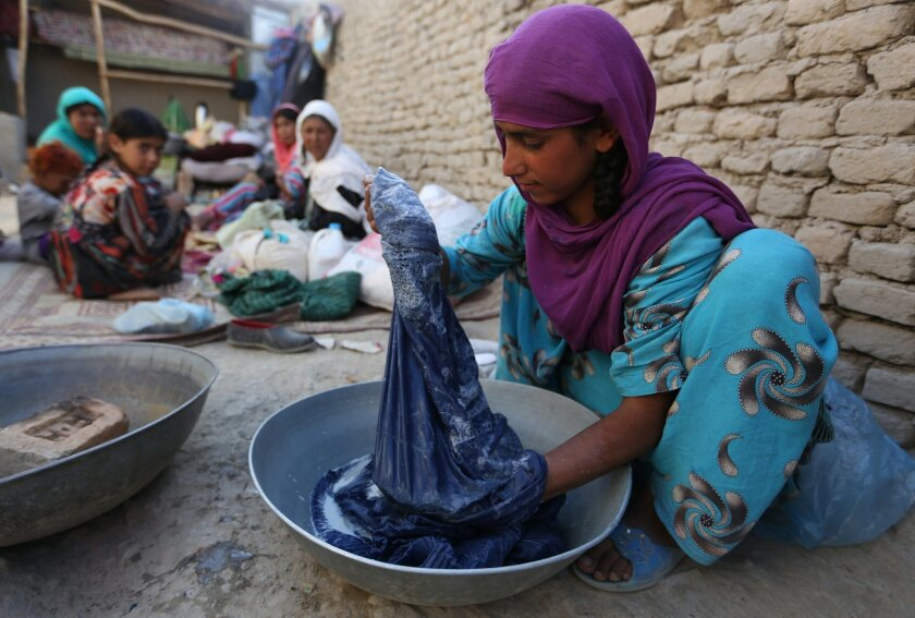 In this Monday, May 30, 2016 photo, an Afghan girl washes cloths at her temporary home in a camp for internally displaced people in Kabul, Afghanistan. Amnesty International said Tuesday, May 31, that more than 1.2 million Afghans have been forced to flee their homes due to violence in the past thr