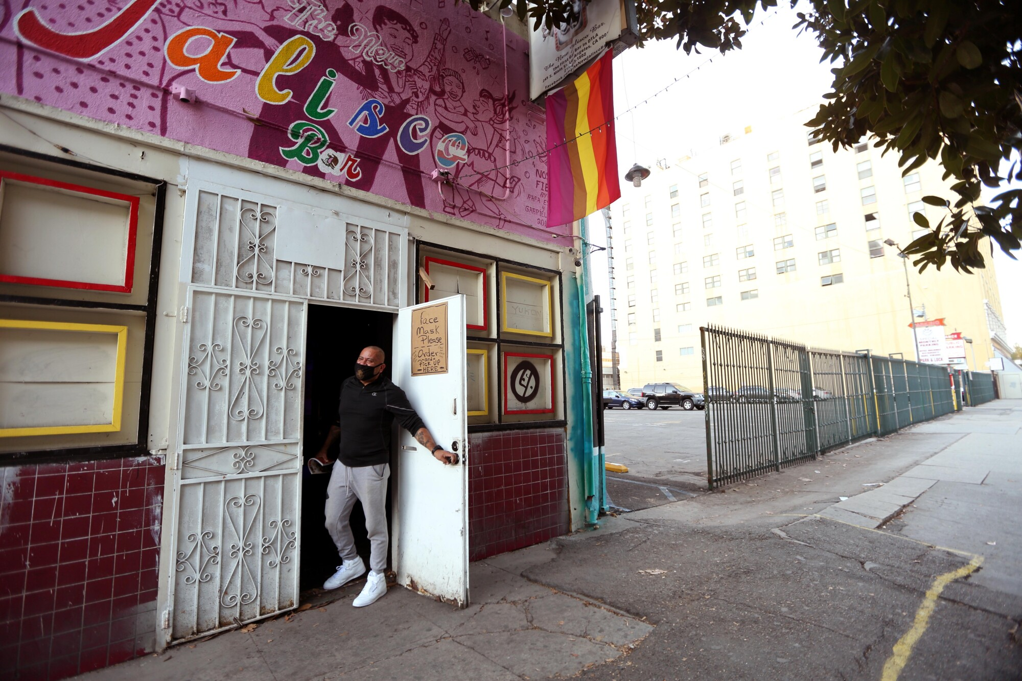 Sergio Hernandez, co-owner of the New Jalisco Bar, looks out the front door of the closed establishment.