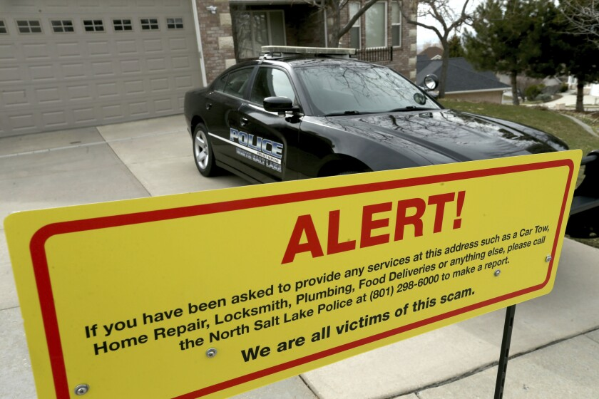 A warning sign and a police officer's vehicle at Walt Gilmore's home in North Salt Lake, Utah, in March.