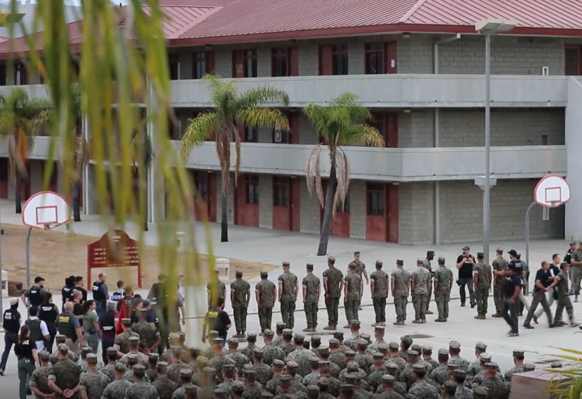 In this video screenshot, NCIS agents and other law enforcement approach the Marines in front of the battalion formation at Camp Pendleton.